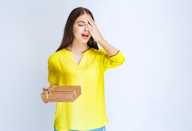 Vrouw die een kartonnen geschenkdoos vasthoudt en er verward of attent uitziet.