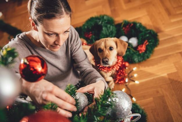 Vrouw die een kerstboom verfraait