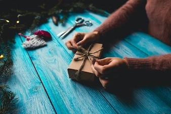 Vrouw die een Kerstmis huidig op blauwe houten achtergrond inpakken