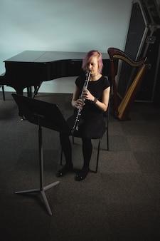 Vrouw die een klarinet in muziekschool speelt