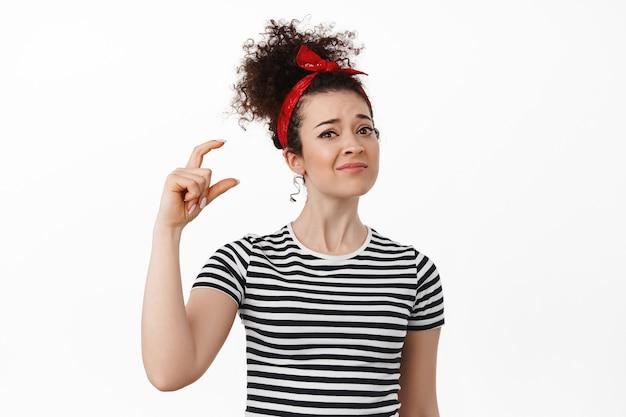 Vrouw die een klein ding laat zien en er teleurgesteld uitziet, een klein, absurd item uitscheldt met een vinger, ontevreden grimassen trekt, over wit staat