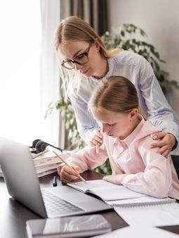 Vrouw die een klein meisje helpt dat haar huiswerk doet