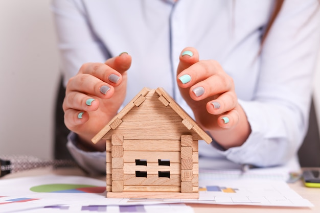 Vrouw die een kleine huisveiligheid met haar handen geeft als dak
