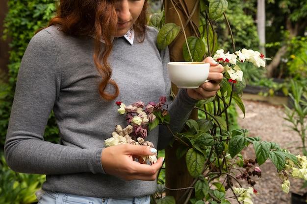 Vrouw die een koffiekop en bloemen houdt