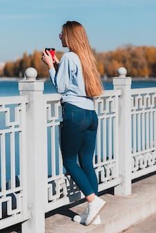 Vrouw die een koffiekop houdt en op traliewerk rust
