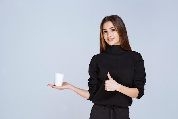 Vrouw die een koffiekopje vasthoudt en geniet van de smaak.