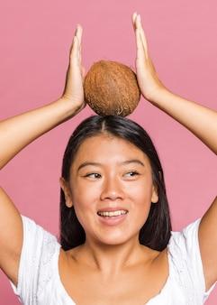 Vrouw die een kokosnoot op haar hoofd houdt