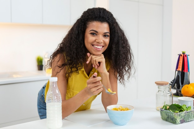 Vrouw die een kom granen met melk voorbereidt