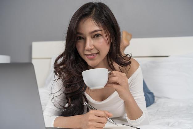 Vrouw die een kop van koffie drinkt en laptop computer op bed met behulp van