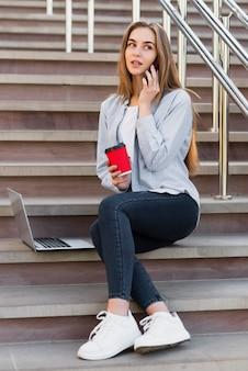Vrouw die een kop van koffie houdt en op telefoon spreekt