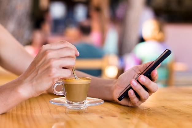 Vrouw die een kop van koffie in een terras in openlucht hebben en mobiele telefoon met behulp van.