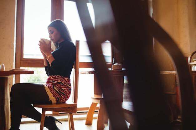 Vrouw die een kop van koffie in koffie heeft