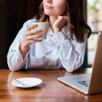Vrouw die een kop van koffie met laptop op bureau houdt