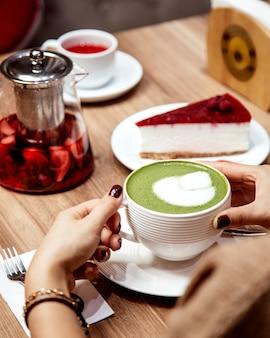 Vrouw die een kop van matcha groene thee met lattekunst drinkt