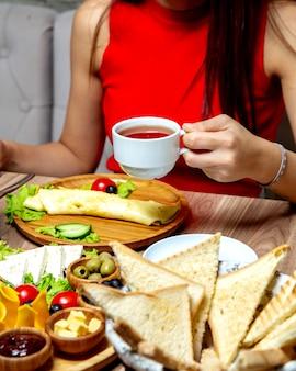 Vrouw die een kop van zwarte thee drinkt die voor ontbijt wordt gediend