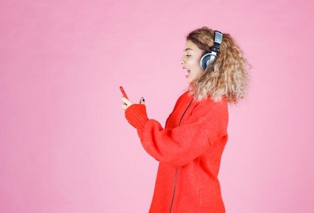 Vrouw die een koptelefoon draagt, luistert naar haar afspeellijst op smartphone en danst.