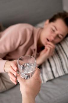 Vrouw die een koud ontvangend water en pillen heeft