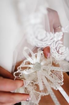 Vrouw die een kousenband op het been draagt. de bruid houdt een losse kousenband in de hotelkamer in de hand. ochtend voorbereiding bruiloft concept.