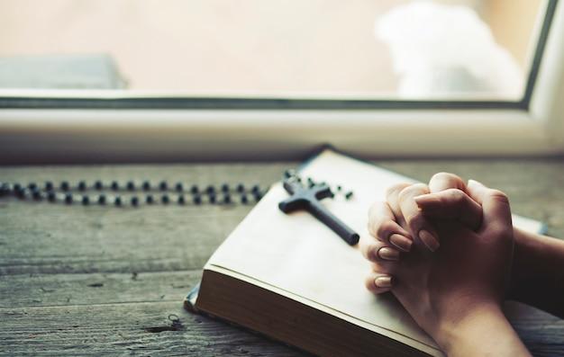 Vrouw die een kruis houdt terwijl bidt