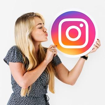 Vrouw die een kus blaast aan een instagram-pictogram