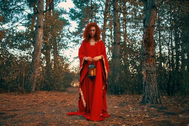 Vrouw die een lantaarn met een kaars houdt.