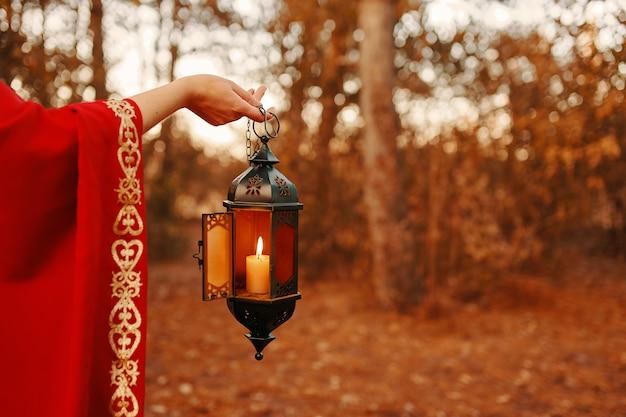 Vrouw die een lantaarn met een kaars in het bos houdt
