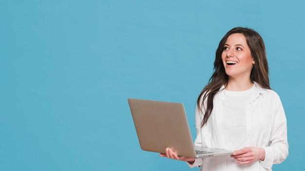 Vrouw die een laptop exemplaarruimte houdt