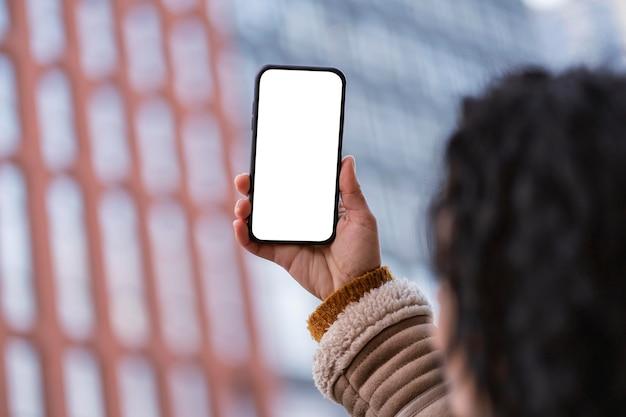 Vrouw die een lege smartphone bekijkt