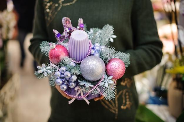 Vrouw die een leuke roze en blauwe tonen van kerstmissamenstelling n houdt die van kaars, spar en glasballen wordt gemaakt