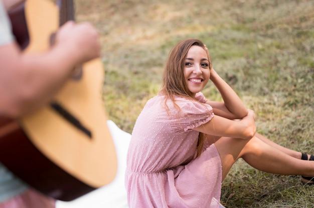 Vrouw die een man bekijkt die gitaar speelt