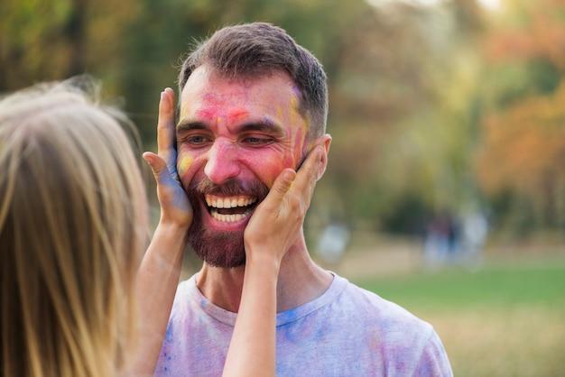 Vrouw die een man gezicht behandelt met verf