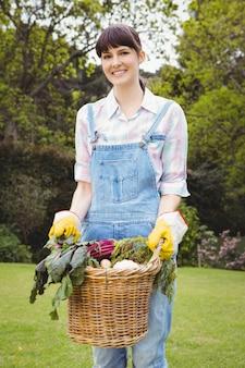 Vrouw die een mand vers geoogste groenten in tuin houdt