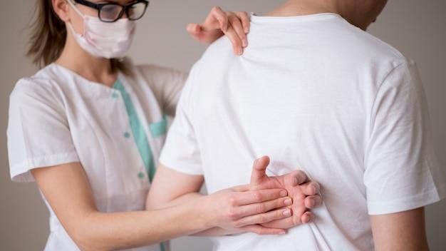 Vrouw die een masker draagt en een patiënt controleert