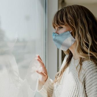 Vrouw die een masker draagt en uit het raam staart tijdens een lockdown
