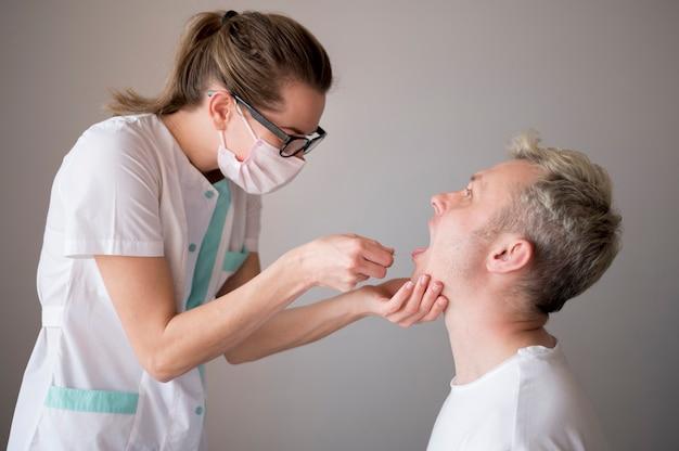 Vrouw die een masker draagt, test een man op virussen