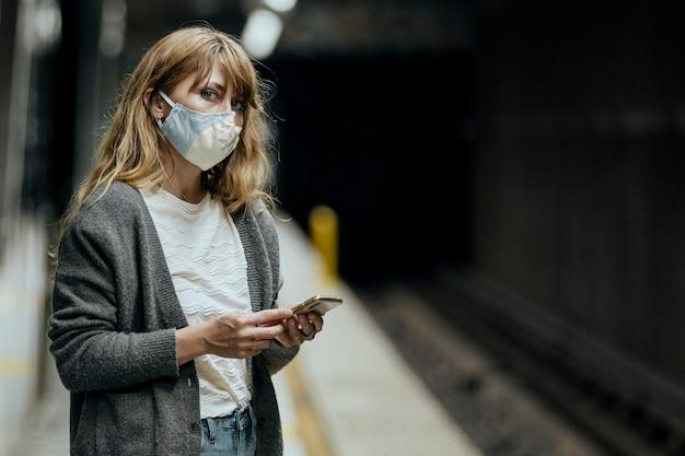 Vrouw die een masker draagt tijdens het wachten op de trein tijdens de pandemie van het coronavirus