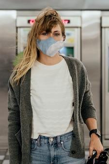 Vrouw die een masker draagt tijdens het wachten op de trein tijdens de pandemie van het coronavirus Premium Foto