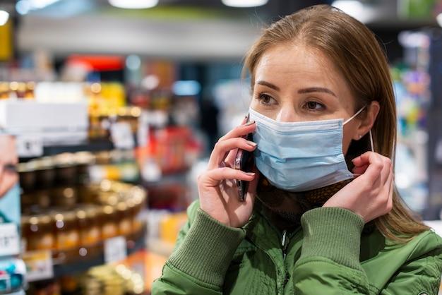 Vrouw die een masker in supermarkt draagt