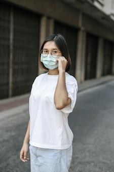 Vrouw die een masker op straat draagt.