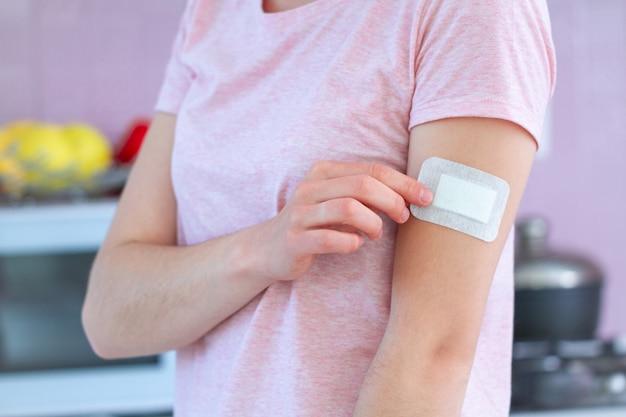 Vrouw die een medisch bactericide zelfklevend verband op wapen na vaccinatie, injectievaccin of geneeskunde gebruikt. eerste hulp bij snijwonden en wonden
