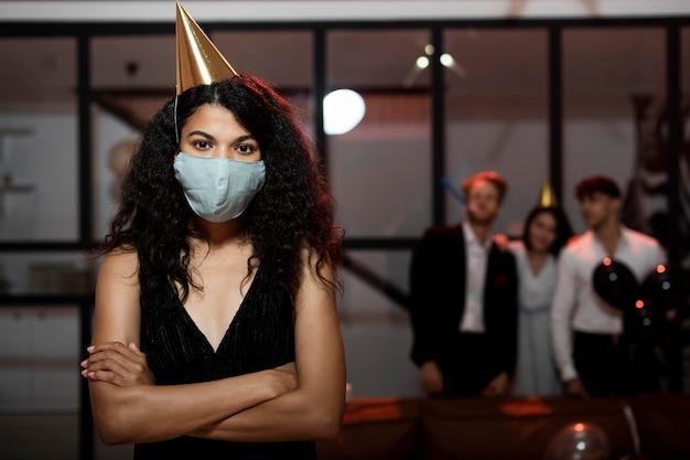 Vrouw die een medisch masker draagt op oudejaarsavondfeest met kopie ruimte