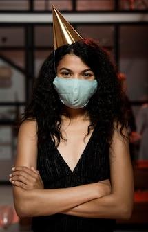 Vrouw die een medisch masker draagt op oudejaarsavondfeest