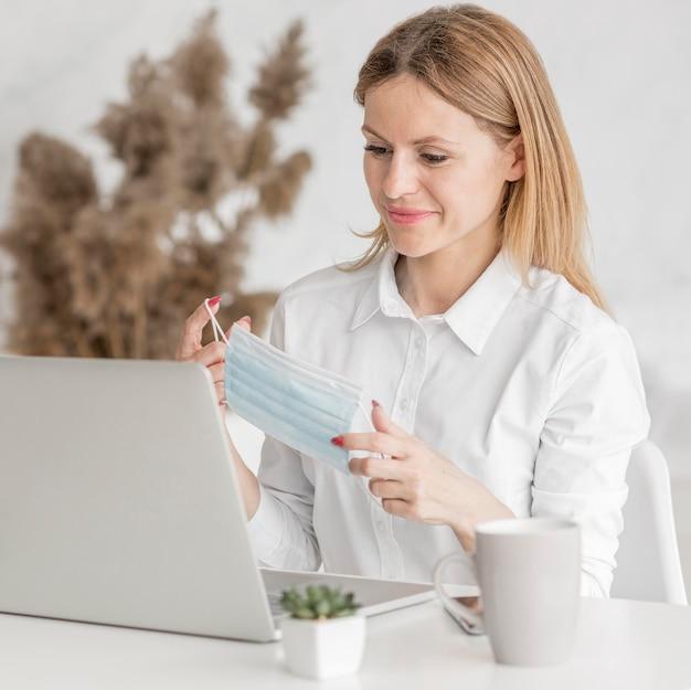 Vrouw die een medisch masker voor haar laptop camera houdt