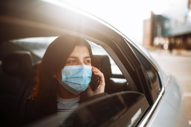 Vrouw die een medisch steriel masker draagt in een taxiauto op een achterbank die uit venster kijkt