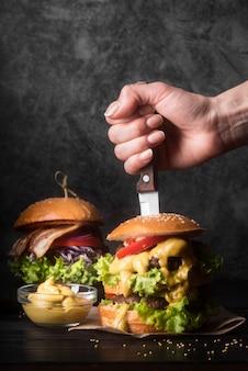 Vrouw die een mes in een smakelijke hamburger houdt