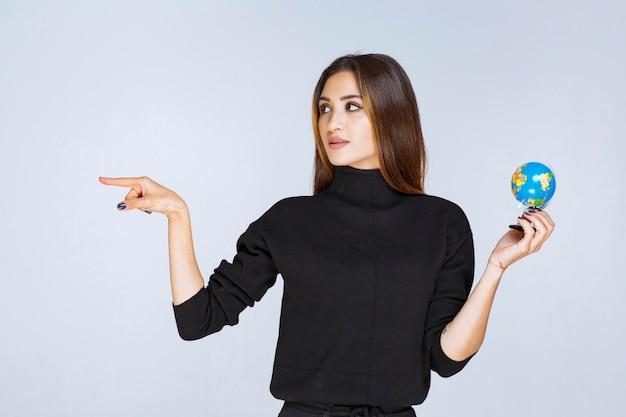 Vrouw die een mini-wereldbol vasthoudt en ergens naar wijst.