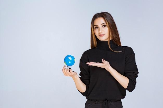 Vrouw die een mini-wereldbol vasthoudt en promoot.
