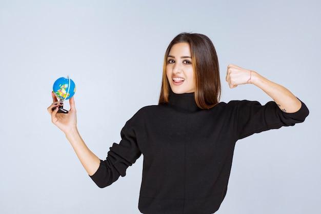 Vrouw die een minibol vasthoudt en haar vuist toont.
