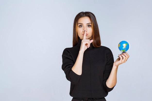 Vrouw die een minibol vasthoudt en om stilte vraagt.