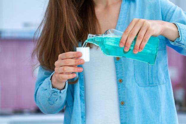 Vrouw die een mondspoeling gebruiken om mond en tandgezondheid te spoelen. mondhygiëne en tandenverzorging